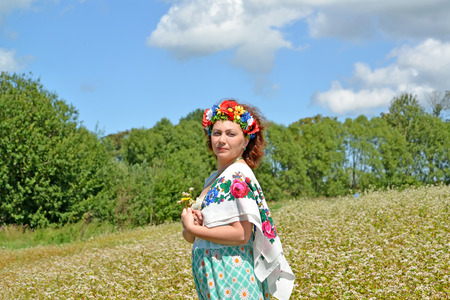 The mature woman with a wreath on the head and a colorful scarf on a shoulder against the background of the blossoming buckwheat field Stock Photo
