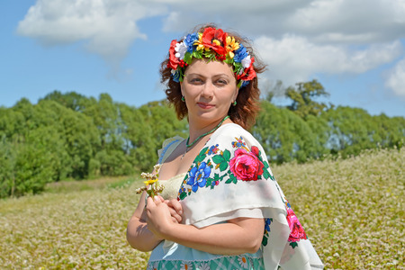 Portrait of the mature woman with a wreath on the head and a colorful scarf on a shoulder against the background of the blossoming buckwheat field