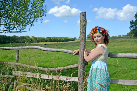 The woman of average years with a wreath on the head stands near a fence