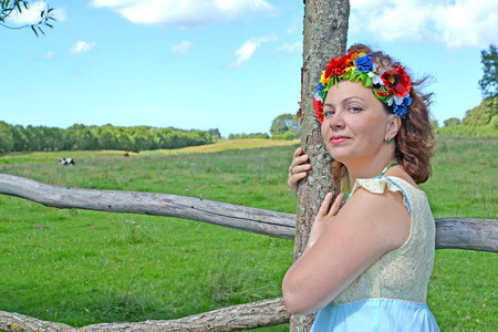 Portrait of the mature woman with a wreath on the head about a fence