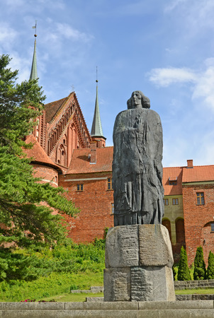 FROMBORK, POLAND - JULY 09, 2015: A monument to Nicolaus Copernicus against the background of a cathedral complex Stock Photo