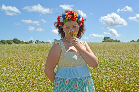 The mature woman with a wreath on the head smells flowers against the background of the buckwheat field Stock Photo