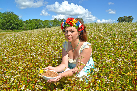 The beautiful woman of average years with a wreath on the head holds a bowl with buckwheat in the field of the blossoming buckwheat Фото со стока