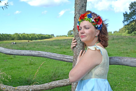 Portrait of the beautiful mature woman with a wreath on the head about a fence Stock Photo