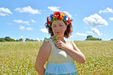 The woman of average years with a wreath on the head holds flowers against the background of the buckwheat field Фото со стока