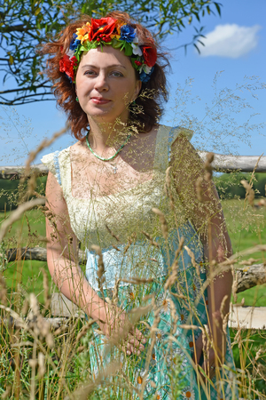 The woman with a wreath on the head costs among a field grass