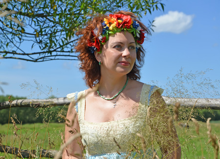 Portrait of the mature woman with a wreath on the head against the background of the sky Stock Photo