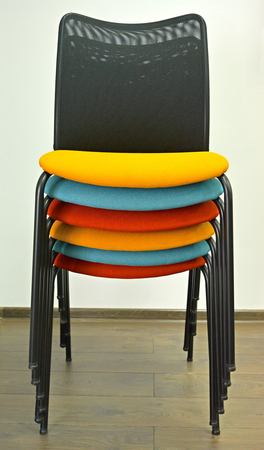 Office chairs are put with color semi-soft seats in a stack