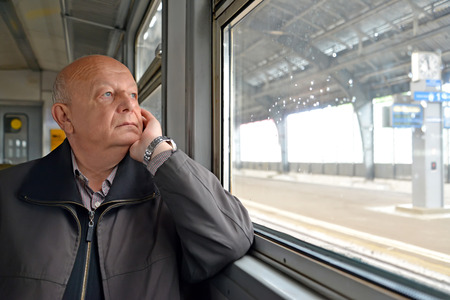 The male pensioner thoughtfully looks out of the electric train window