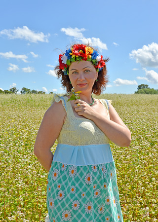 The mature woman with a wreath on the head holds flowers against the background of the buckwheat field Stock Photo