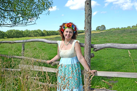 The cheerful woman with a wreath on the head stands near a fence