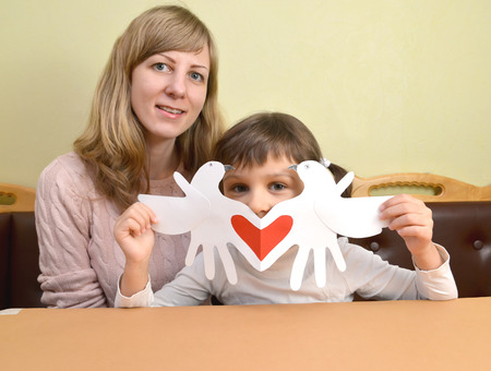 The young woman and the cheerful little daughter with a self-made gift card Valentines Day card