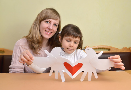 The young woman and the little daughter with a self-made gift card Valentines Day card