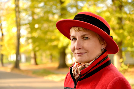 The womans portrait in a red hat on the autumn street
