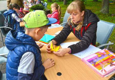 KALININGRAD, RUSSIA - SEPTEMBER 17, 2017: The teacher teaches the boy to put origami. Childrens master class in the open air