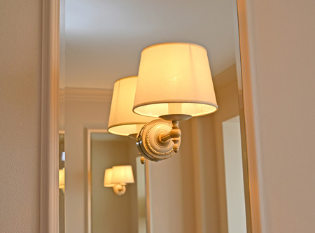 The sconce is mounted on a mirror panel