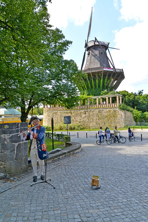 POTSDAM, GERMANY - AUGUST 14, 2017: The musician in an ancient suit plays a flute in the Sanssousi park Редакционное