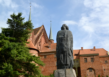 FROMBORK, POLAND - JULY 09, 2015: A monument to the scientist Nicolaus Copernicus against the background of a cathedral complex