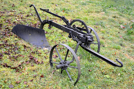The old plow on horse draft lies on a grass