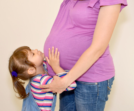 The little girl  on a stomach of pregnant mother Stock Photo