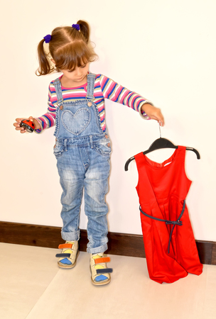 The little girl holds a beautiful red dress on a hanger