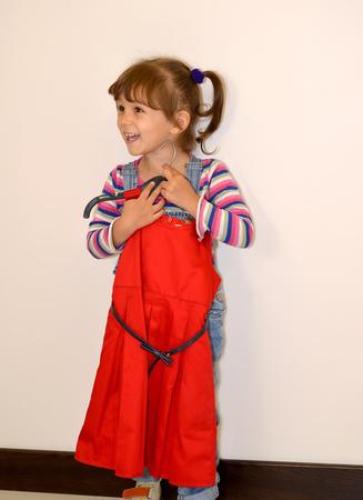 The little joyful girl tries on a beautiful red dress