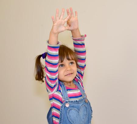 The little girl raises hands up