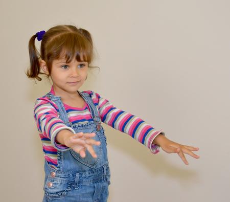 The little girl extends hands forward