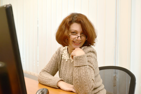 The business woman with a smile looks over  glasses Stock Photo