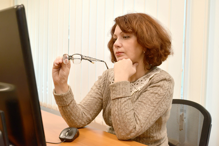 The woman looks in the computer monitor, holding glasses in hand Stock Photo