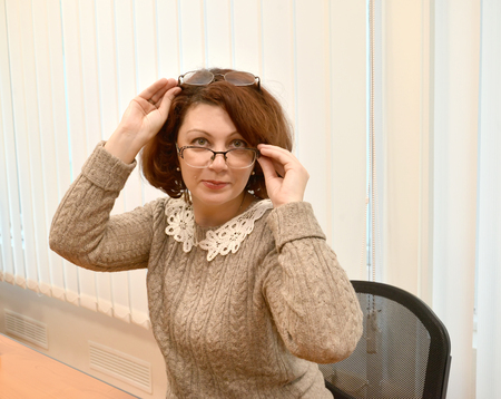 The business woman with a smile looks over glasses, holding the second glasses on the head