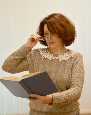 The woman of average years reads the book on an outstretched arm over glasses