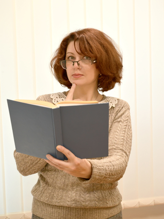 The woman wearing spectacles and the book in a hand thoughtfully looks forward