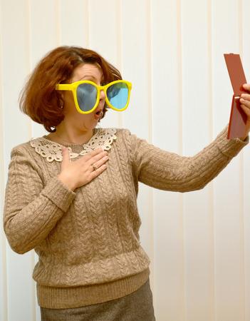 The woman in big sunglasses with surprise looks at herself in a mirror