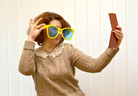 The coquettish woman in big sunglasses smiles, looking at herself in a mirror Stock Photo