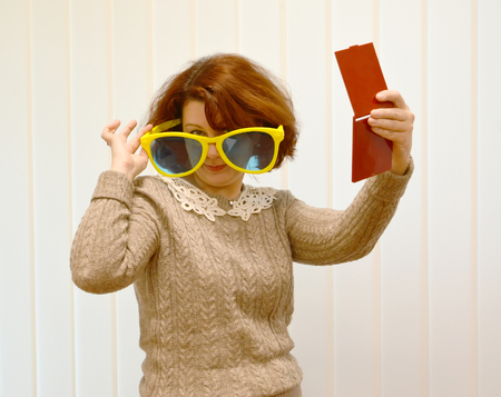 The woman with a mirror in a hand looks over big sunglasses