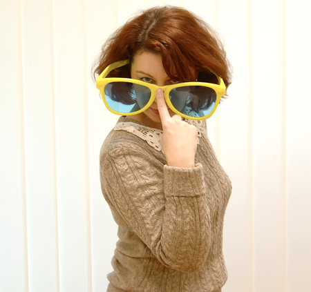 The woman lours over big sunglasses, holding them with a finger Stock Photo