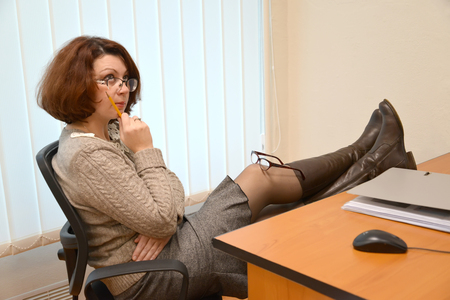The thoughtful woman sits at office with legs on a table and glasses on a knee