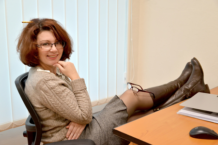 The cheerful woman sits at office with legs on a table and glasses on a knee