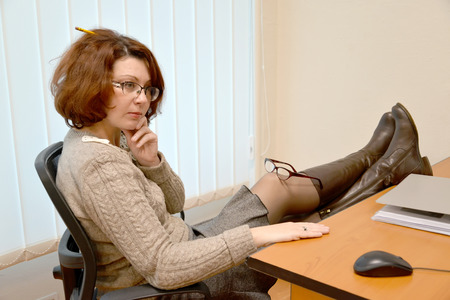 The woman of average years sits at office with legs on a table and  glasses on a knee