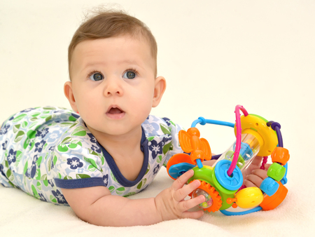 Portrait of the surprised baby with a toy on a light background