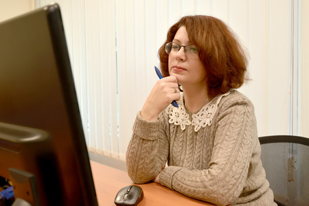 The woman with interest looks in the computer monitor