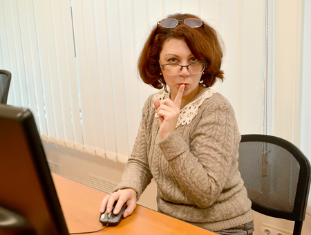 The business woman with a forefinger at lips keeps a secret