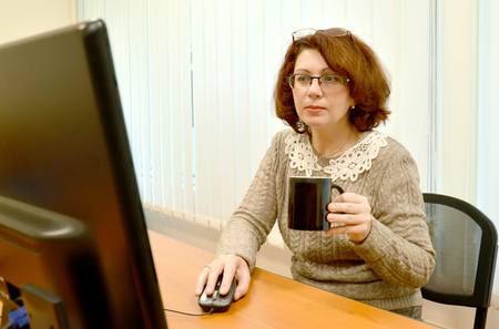 The female manager with a mug in a hand looks in the computer monitor Stock Photo