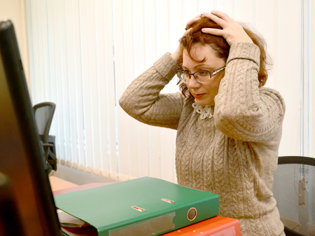 The woman in panic has clasped with hands the head, looking in the monitor Stock Photo