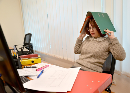 The woman with horror looks in the monitor, holding the folder with documents on the head