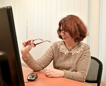 The business woman wearing spectacles looks in the computer monitor through the second points