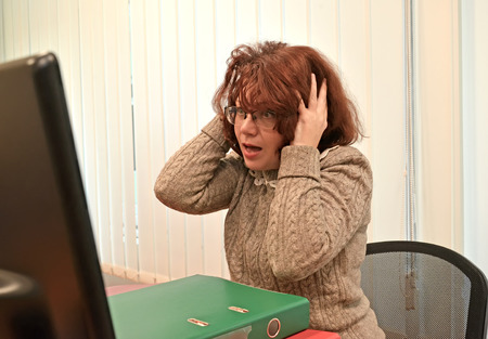 The woman in horror looks in the monitor, having clasped the head with hands