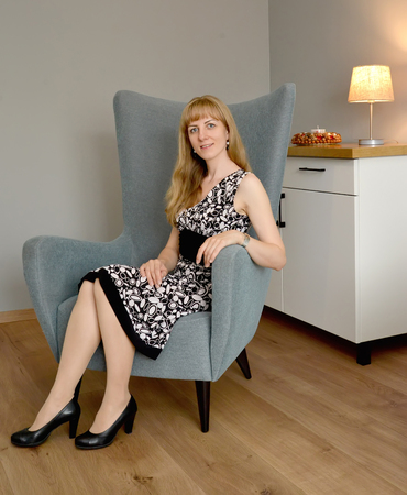 The young woman sits in a chair in the living room Stock Photo