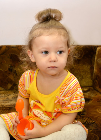 Portrait of the little serious girl with toys in hands